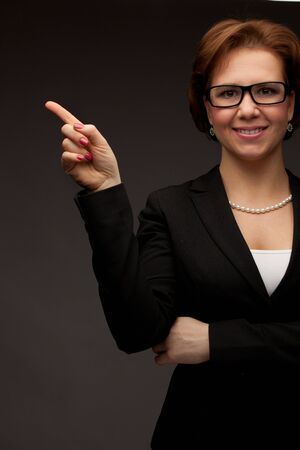 Young beautiful business woman pointing at copyspace photo