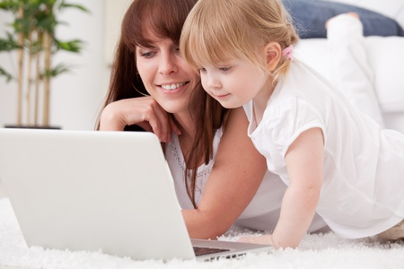 Happy young mother and her  daughter using a laptop photo