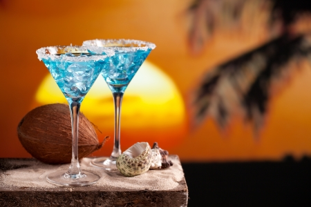two blue cocktail on beach, sunset, palm tree, coconut photo