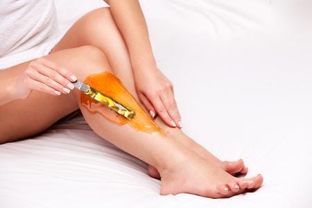 depilaciones: aplicar cera a las mujeres la pierna para eliminar el pelo largo de color blanco