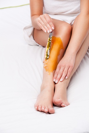 painfully: applying wax to females leg to remove hair over white