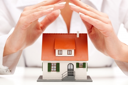 household insurance: Female hands saving small house with a roof