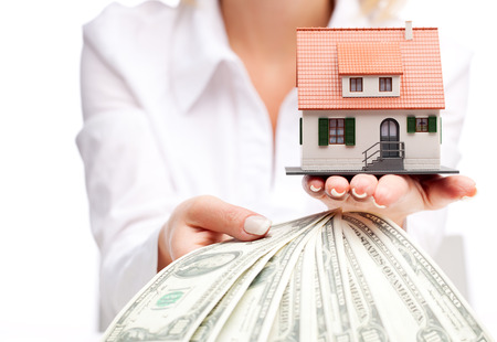 Hands with money and miniature house on a white background Banque d'images