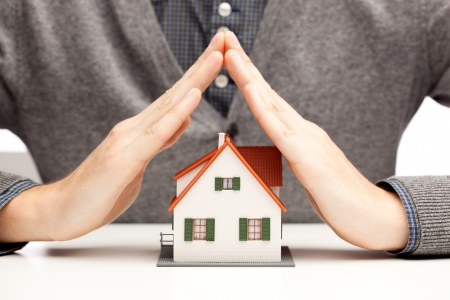 household insurance: Hands as a protecting roof over a little house over white