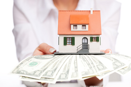 pile of papers: Hands with money and miniature house on a white background Stock Photo