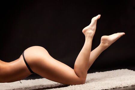 A picture of a sexy woman lying over dark background photo