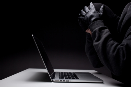 Computer hacker in a balaclava working in the darkness stealing data and personal identity information off a laptop computer Banque d'images