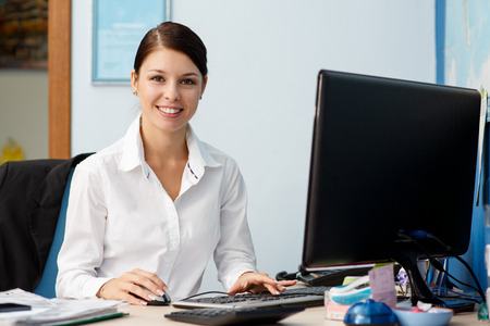 office documents: Young pretty business woman at workplace in office