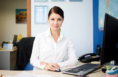 Young pretty business woman at workplace in office photo