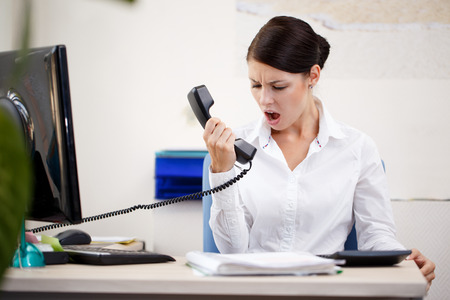 Angry woman shouting at phone Standard-Bild