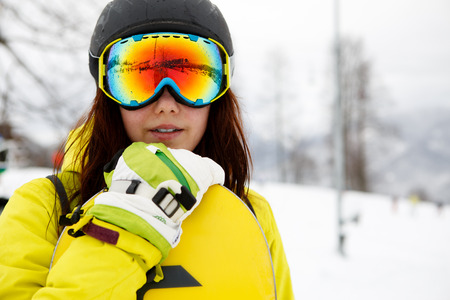 beautiful young woman posing outdoors with her snowboarding gear photo