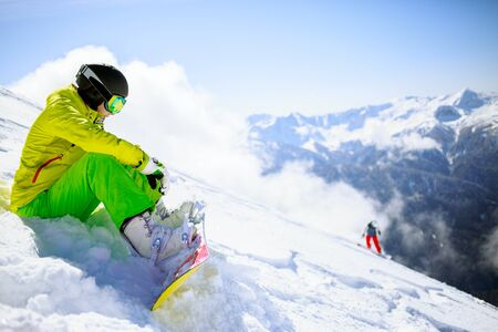 skying: Snowboarder sitting with mountain chain in the background Stock Photo