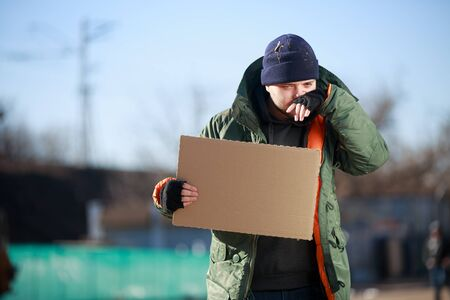 dearth: Homeless man holds blank cardboard for your own text
