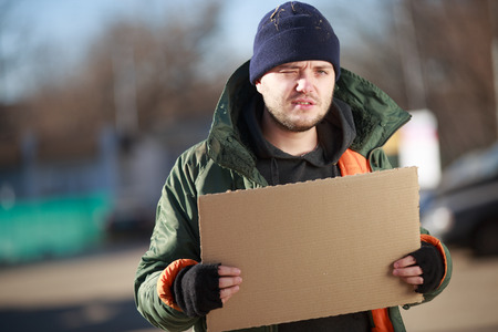 mendicant: Homeless man holds blank cardboard for your own text