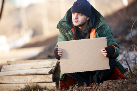 vagabundos: El hombre sin hogar mantiene cartón en blanco para el texto