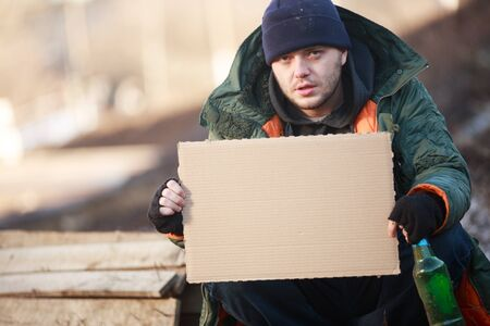 paucity: Homeless man holds blank cardboard for your text
