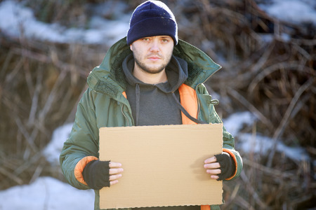 hard times: Homeless man holds blank cardboard for your text