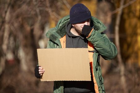 paucity: Homeless man holds blank cardboard for your own text