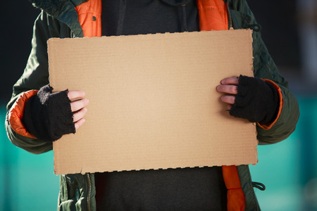 ホームレスの男性は、独自のテキストを空の段ボールを保持しています。 写真素材