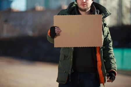 disparity: Homeless man holds blank cardboard for your own text