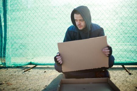 mendicant: Homeless man holds blank cardboard for your text