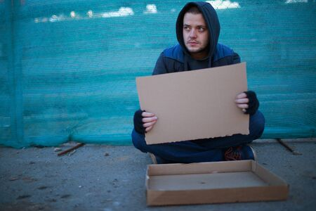 scourge: Homeless man holds blank cardboard for your text