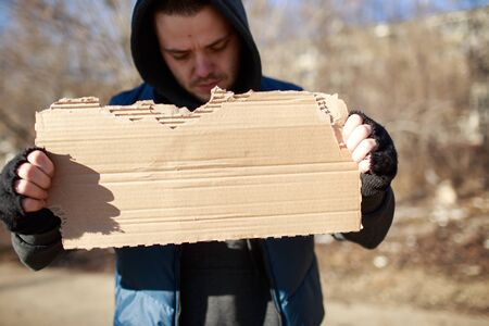 transient: Homeless man holds blank cardboard for your text