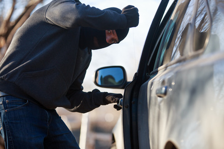 scammer: Thief stealing automobile car at daylight street in city
