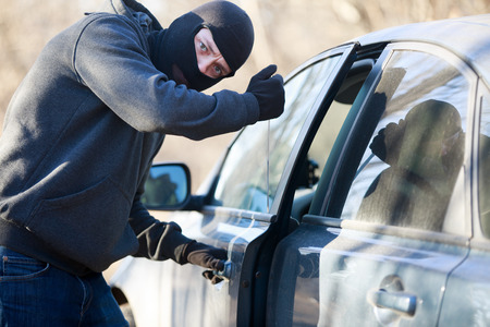 social apartment: Thief stealing automobile car at daylight street in city