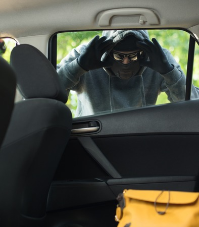 swindler: Transportation crime concept .Thief stealing bag from the car Stock Photo