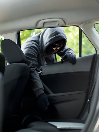 looter: Car theft - a laptop being stolen through the window of an unoccupied car.