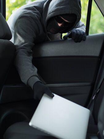 car theft: El robo de autom�viles - un ordenador port�til es robado por la ventana de un coche desocupado.