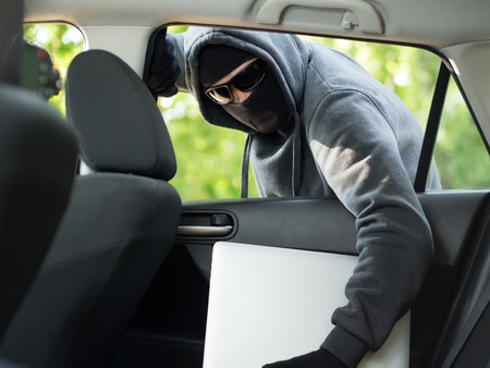 law breaking: Car theft - a laptop being stolen through the window of an unoccupied car.