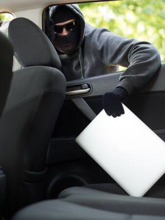 robo de autos: El robo de automóviles - un ordenador portátil es robado por la ventana de un coche desocupado.