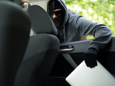 looting: Car theft - a laptop being stolen through the window of an unoccupied car.