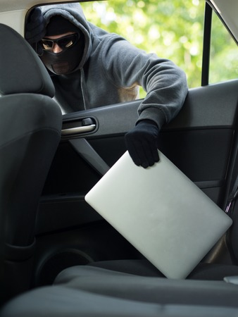 unoccupied: Car theft - a laptop being stolen through the window of an unoccupied car.