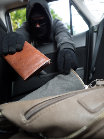 looting: Crime concept. Burglar taking wallet from car.