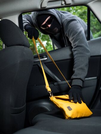 breakin: Transportation crime concept .Thief stealing bag from the car Stock Photo