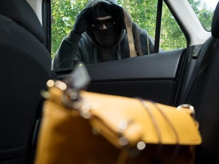 ladron: Transportation crime concept .Thief stealing bag from the car Foto de archivo