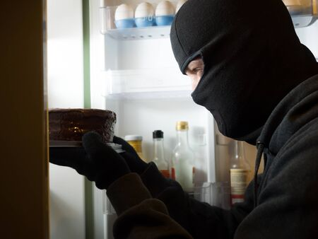 Thief. Man in black mask with a cake. Stock Photo