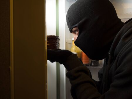 looting: Thief. Man in black mask with a cake. Stock Photo