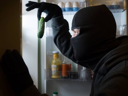 looting: Thief. Man in black mask with a cucumber.