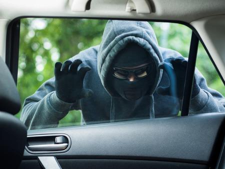 Het concept van het vervoer misdaad .Thief stelen tas uit de auto Stockfoto