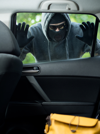 delinquency: Transportation crime concept .Thief stealing bag from the car Stock Photo