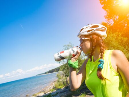 work out: Female athletein cycling helmet drinking water after work out. Stock Photo