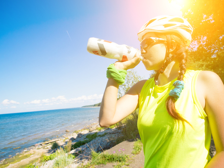 after work: Female athletein cycling helmet drinking water after work out. Stock Photo