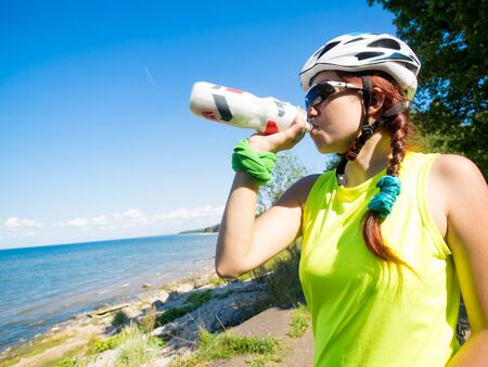 out of water: Female athletein cycling helmet drinking water after work out. Stock Photo