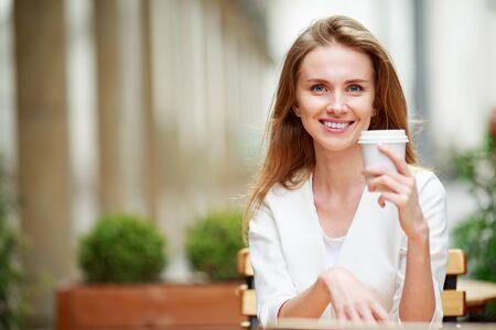 tomando café: Mujer beber café en café de la calle. Luz natural