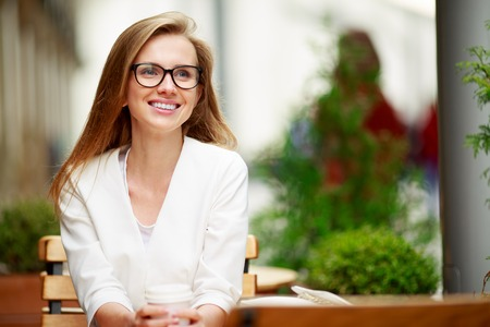 businesswoman suit: Portrait of a smiling business woman, sitting in a street cafe Stock Photo