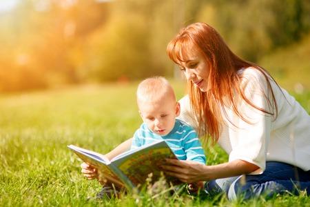 mamá hijo: Madre con el hijo libro de lectura en el parque Foto de archivo